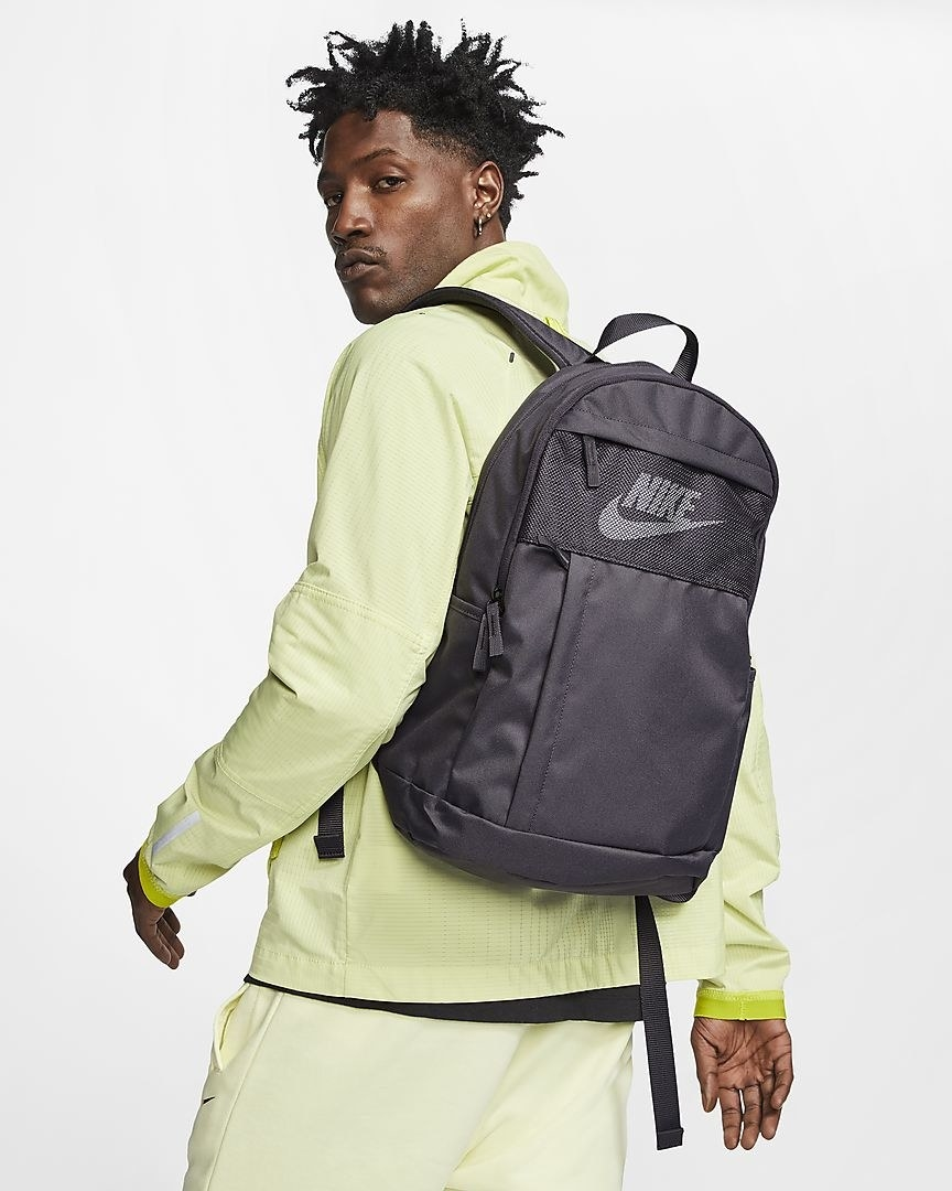 A model carries the Nike Elemental LBR in thunder grey over their shoulder