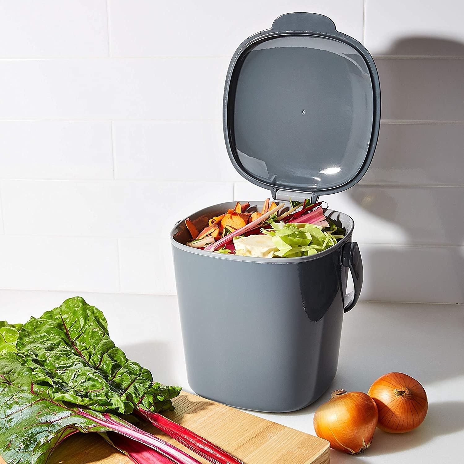 The grey, rounded-corner bin with its lid open, revealing the scraps inside. It has a top handle for easy carrying, and is about as tall with the lid open as the swiss chard sitting next to it