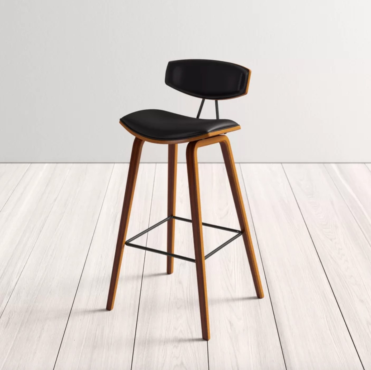 The upholstered stool in black with wood legs