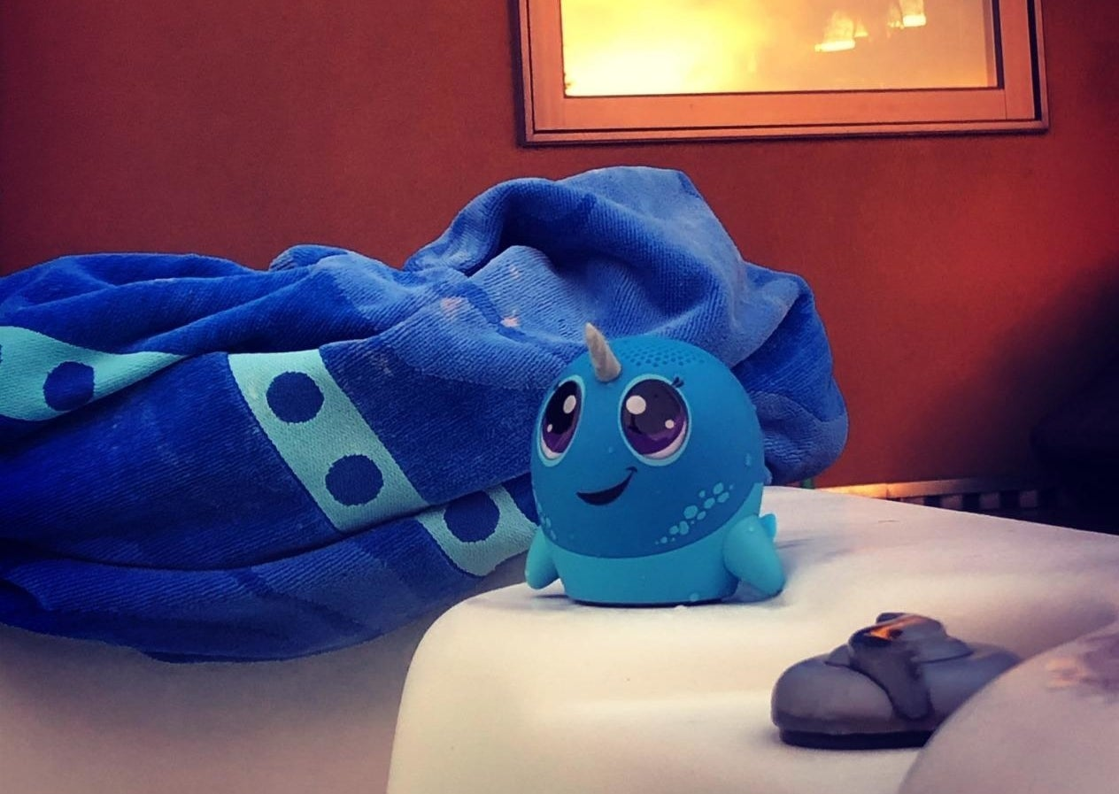Blue plastic narwhal speaker with big cartoon eyes