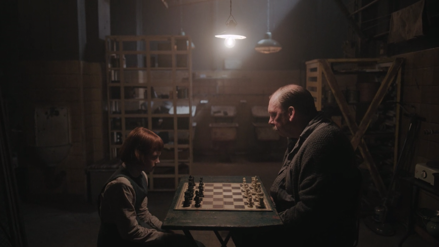 A young Beth Harmon playing chess with and older man