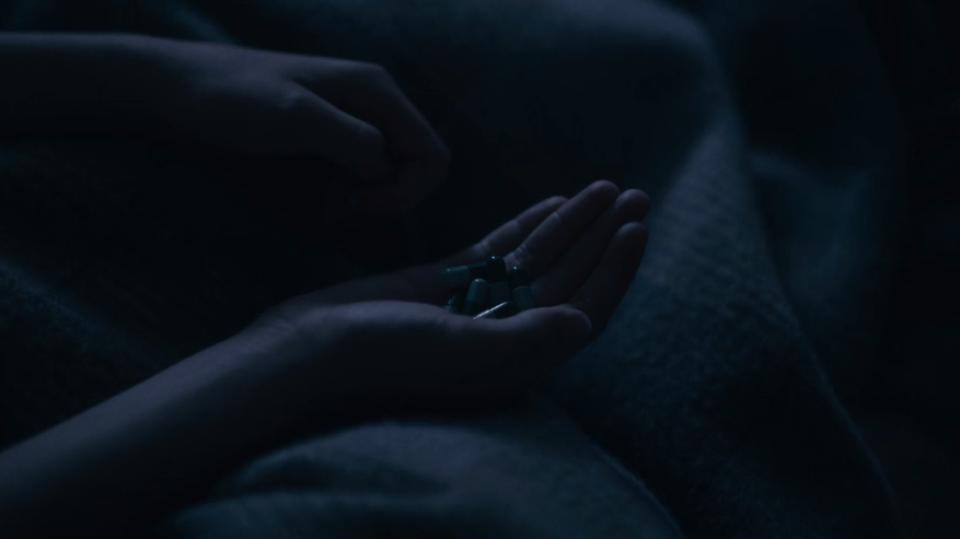 A hand holding pills on top of a blanket