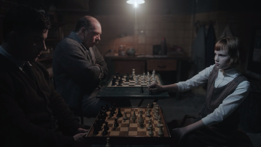 A young Beth Harmon simultaneously playing two games of chess with two men