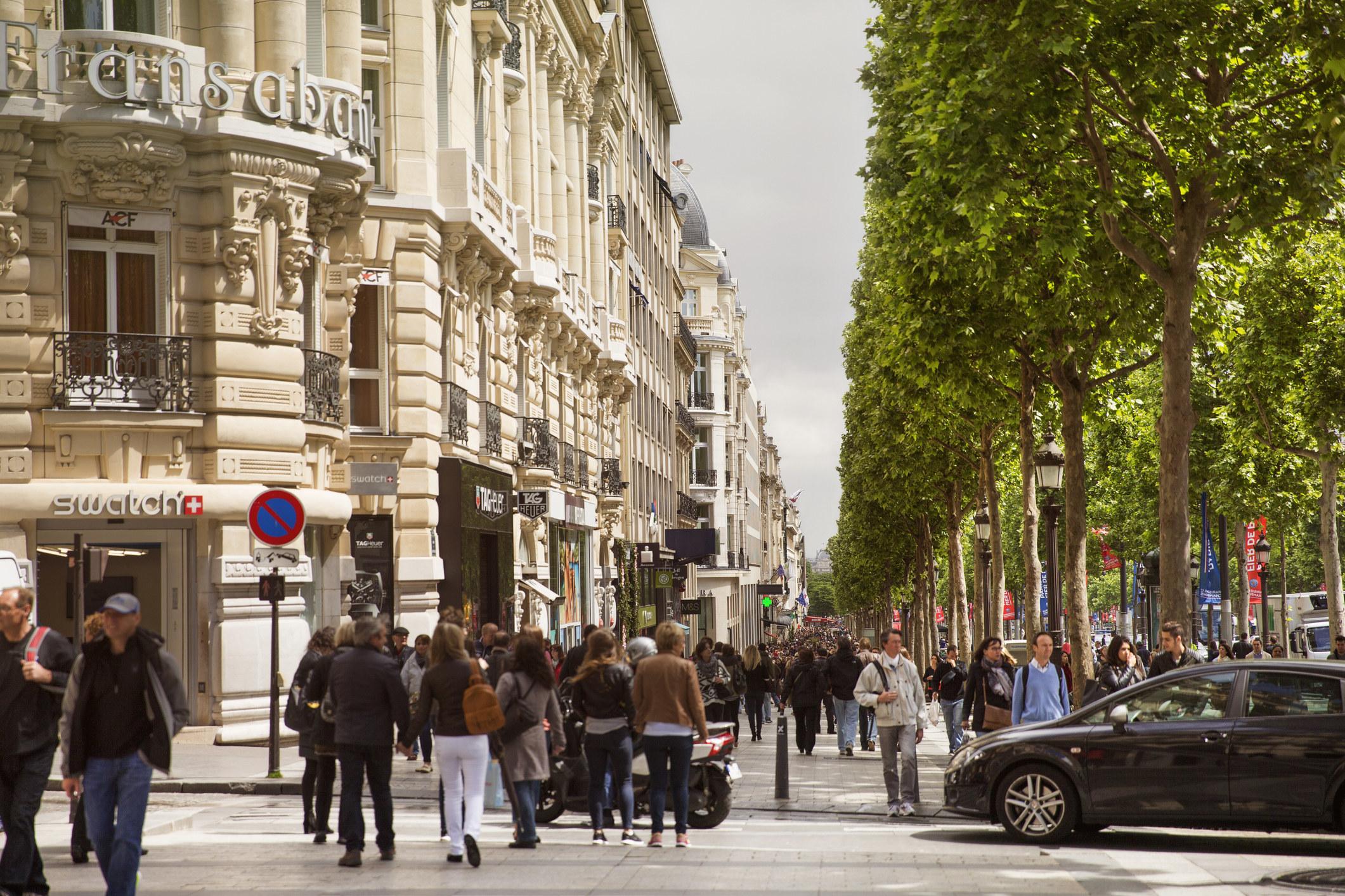 pedestrians walk down the busy Avenue des Champs-Elysees