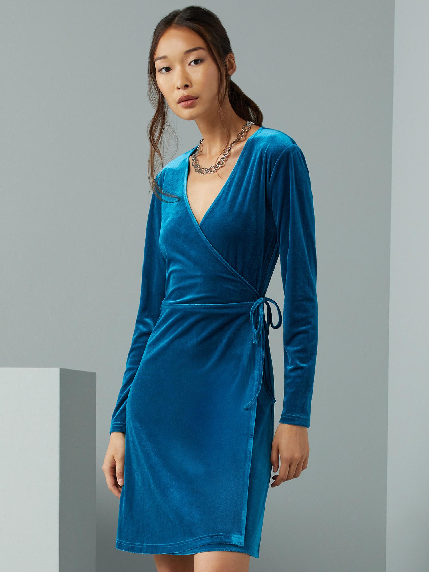 Model wearing blue wrap dress
