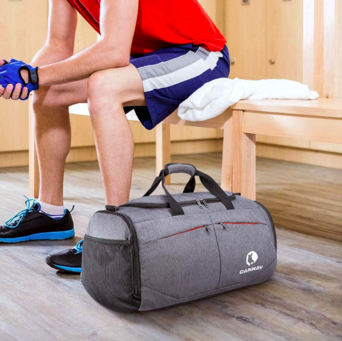 Model sits on gym bench next to gray gym duffle bag with mesh side pockets