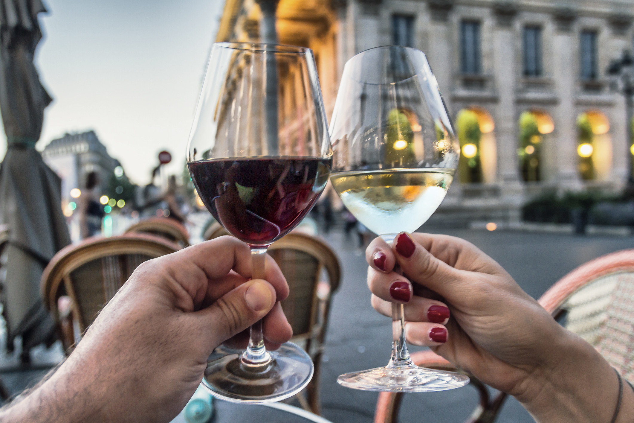 Couple raising glasses with red and white wine in Bordeaux, France