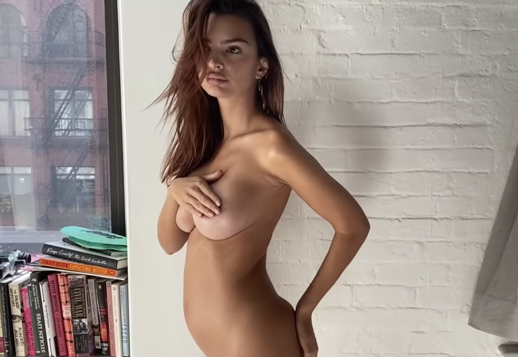 Emily posing nude against a wall with a set of books against a window to the side