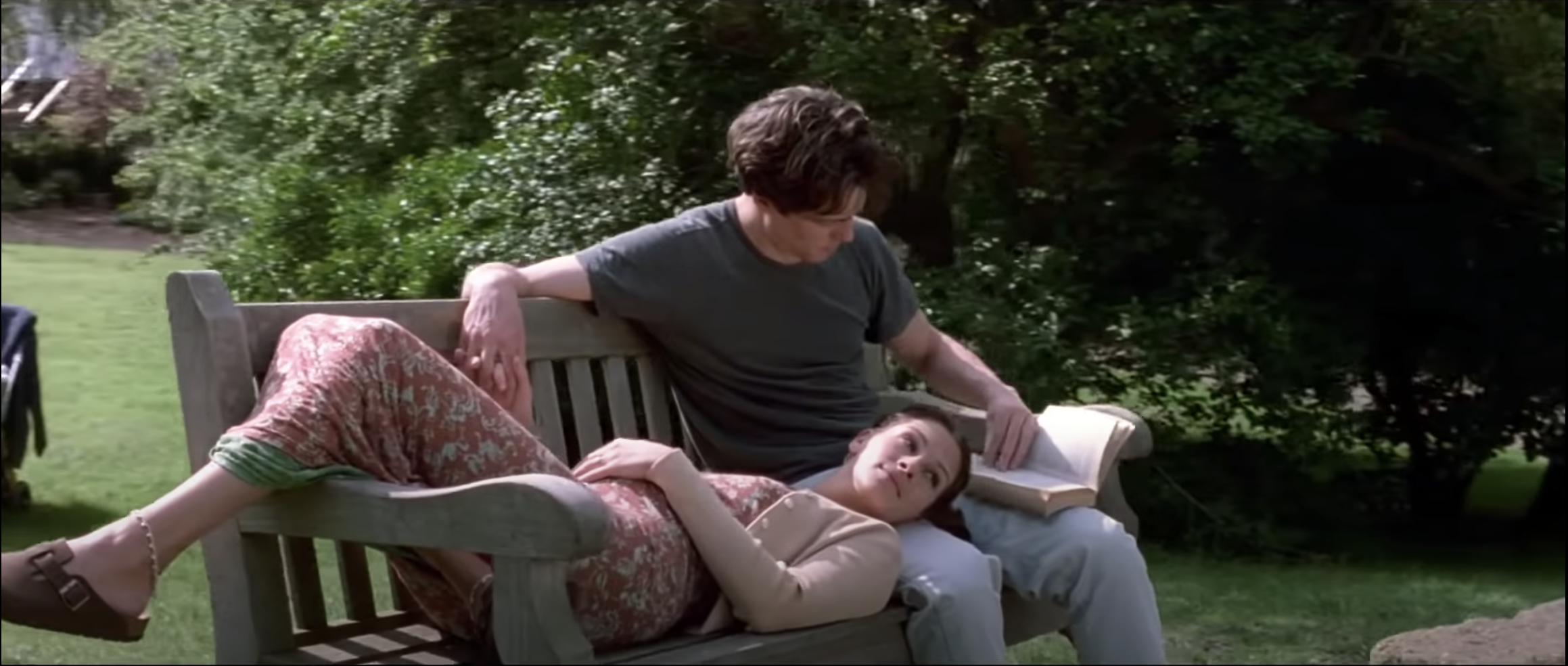 Hugh as Will Thacker sitting on a bench reading to Julia Roberts as Anna Scotts in Notting Hill
