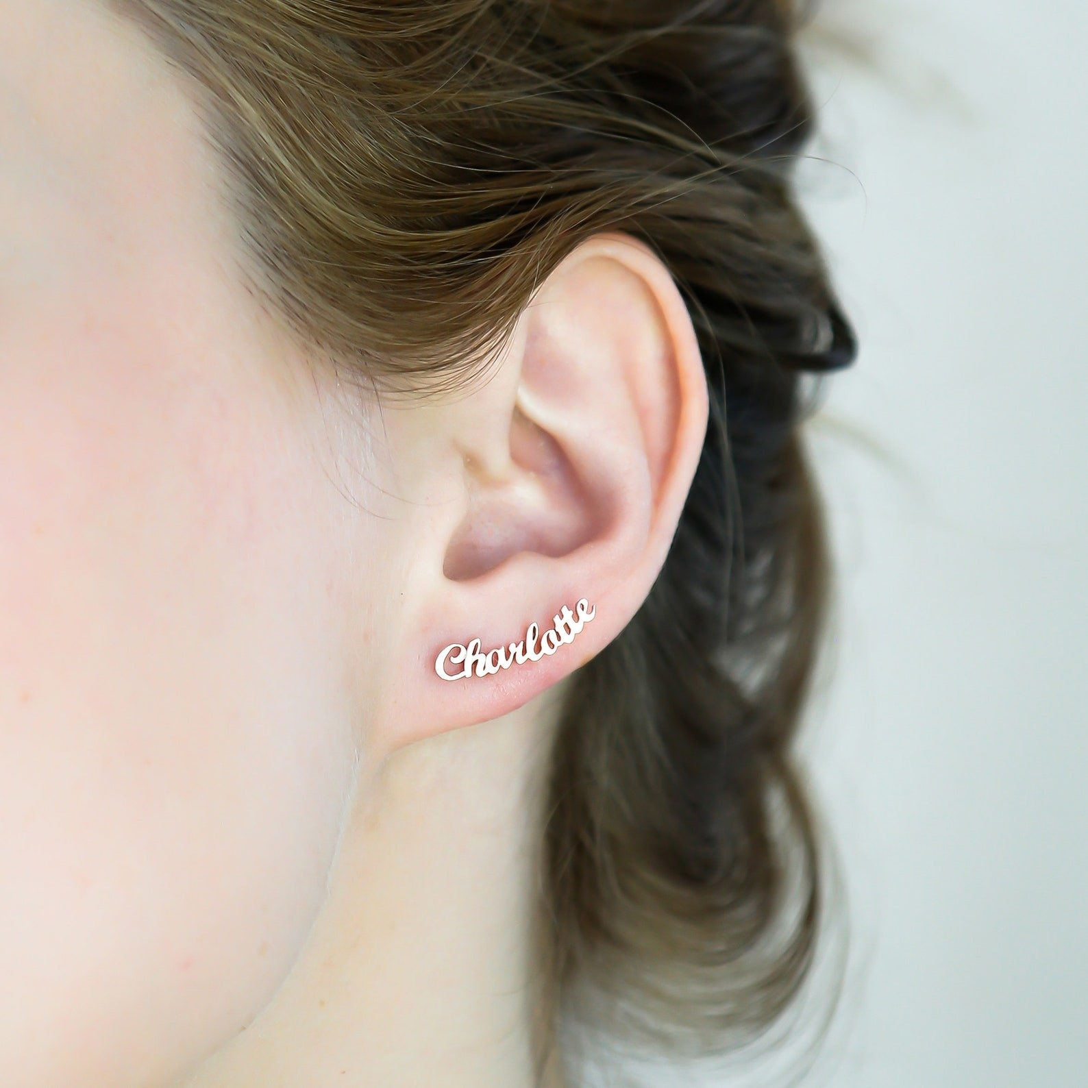 """stud earring that's literally shaped like the name """"charlotte"""" in cursive. It's small enough to fit on the bottom of the earlobe only."""