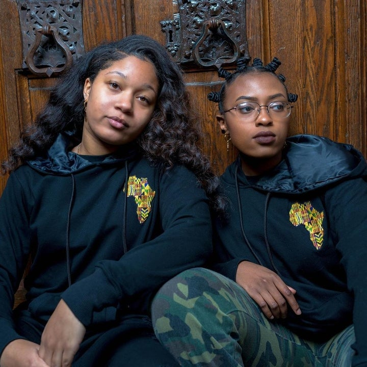 two models wearing the black hoodies with black satin lining in the hoodies and a colorful Africa embroidered on the chest