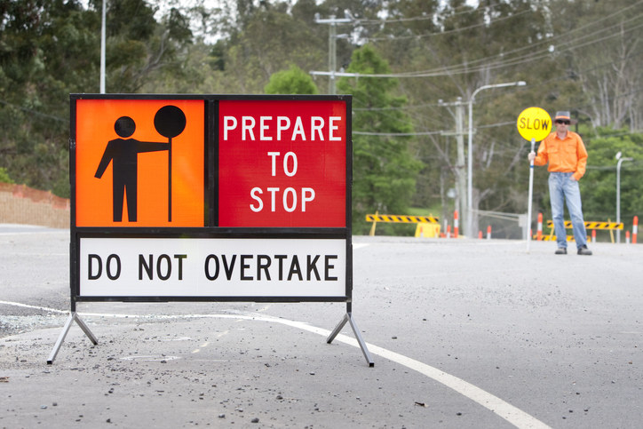 A man holds a slow sign at a roadwork site