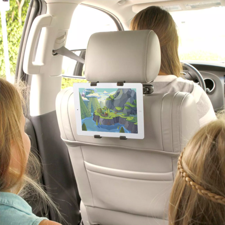 two children watching a show on a tablet in the car