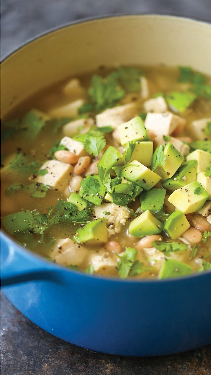 A Dutch oven filled with chunky chicken and white bean stew with avocado and cilantro.