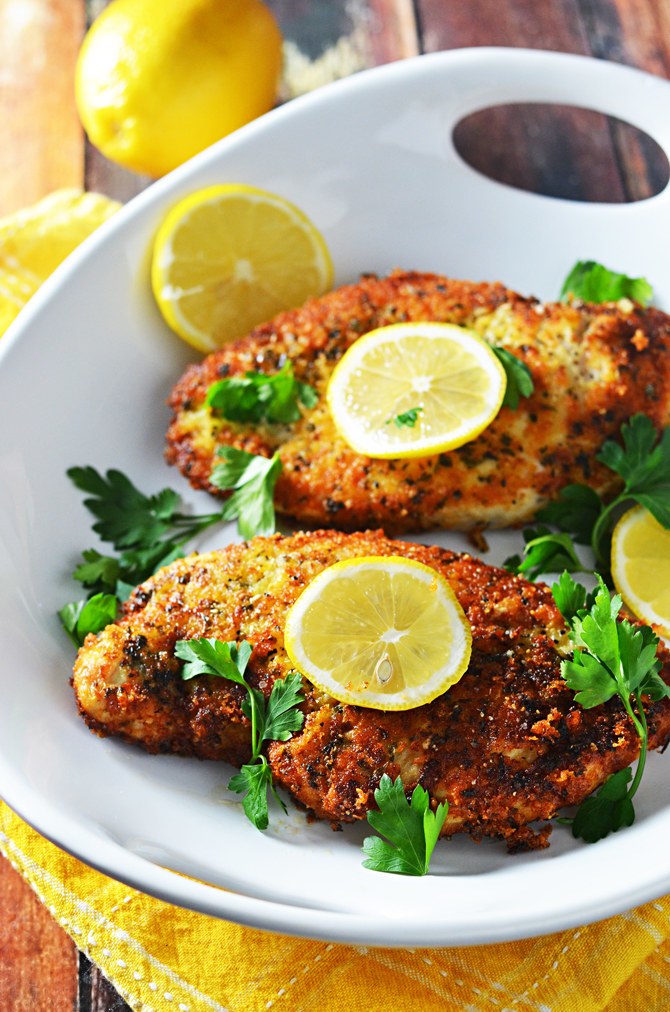 Two crispy lemon chicken cutlets on a plate with fresh herbs.