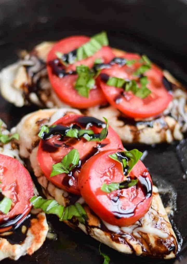 Three chicken breasts topped with tomato, cheese, basil, and balsamic drizzle in a skillet.