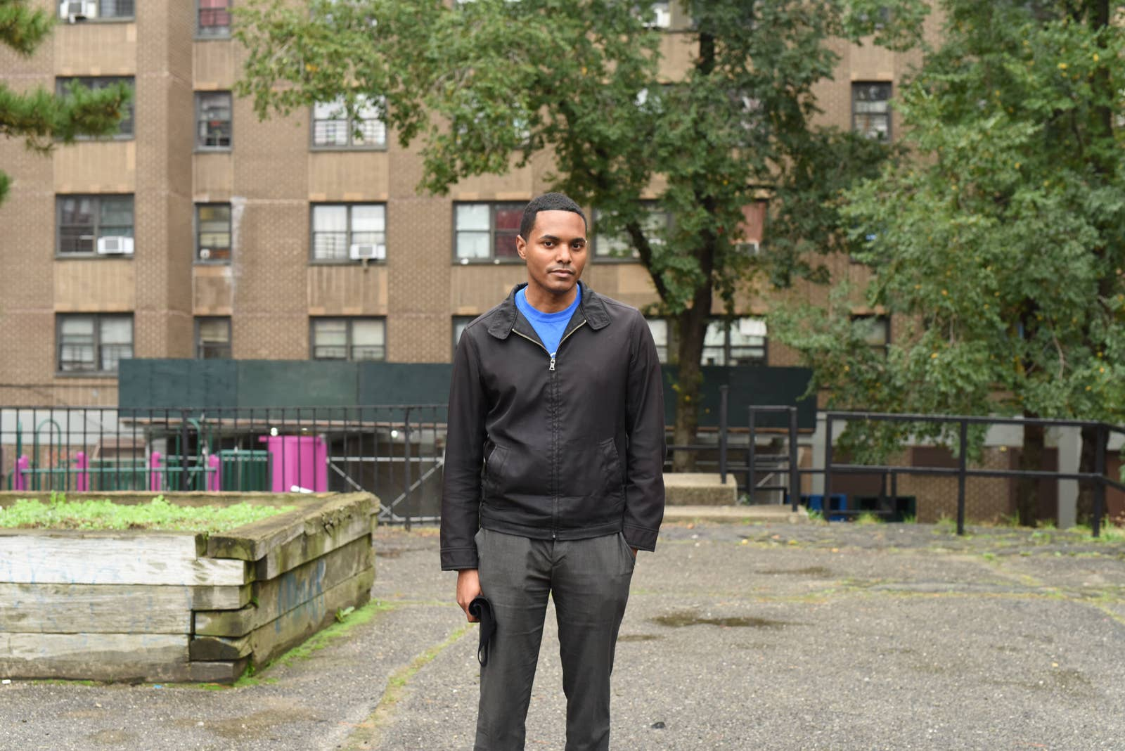 Torres stands in front of a housing project