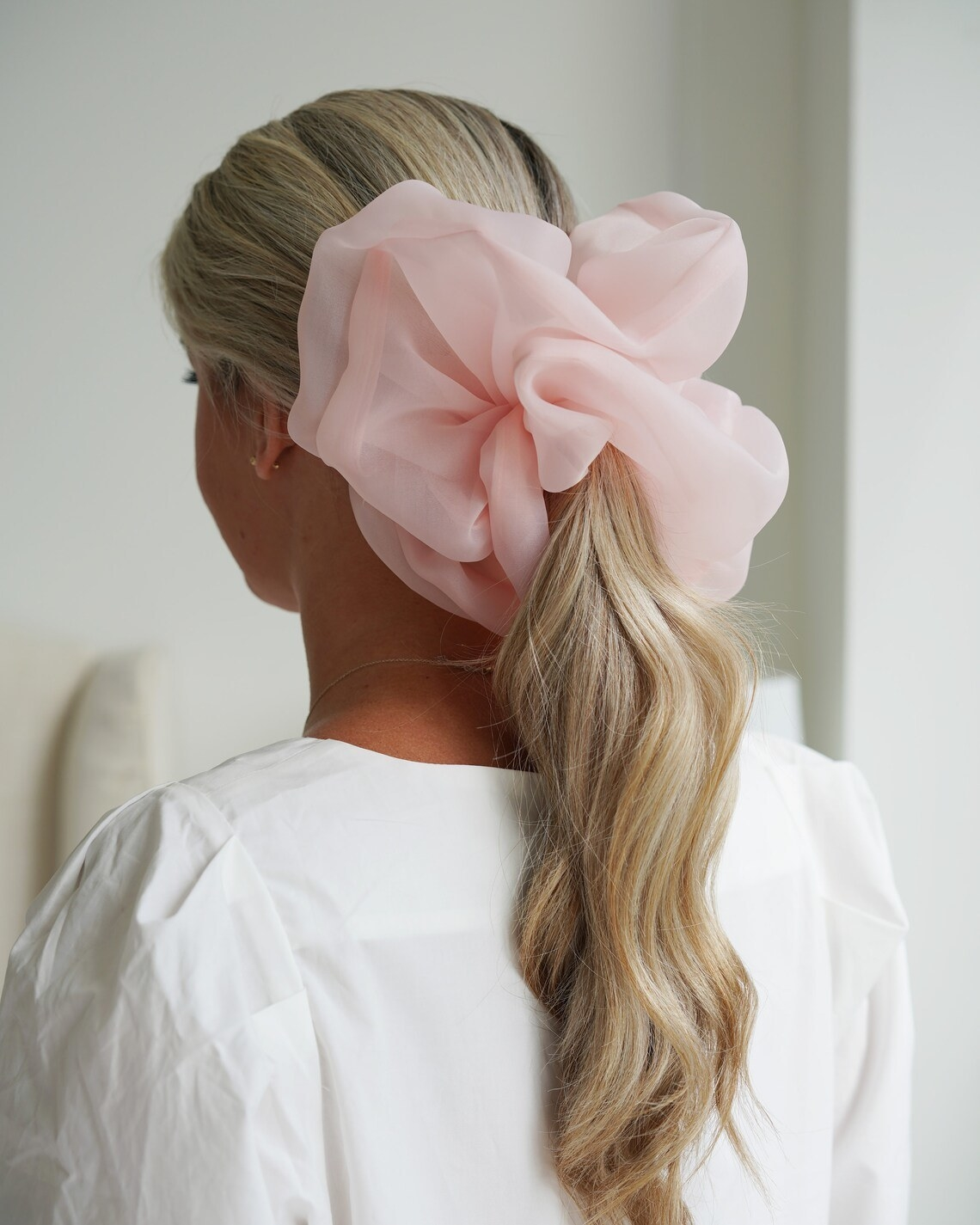 A person wearing their hair in a ponytail using an oversized scrunchie