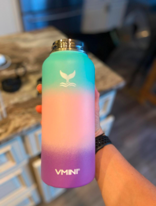 person holding the rainbow gradient water bottle