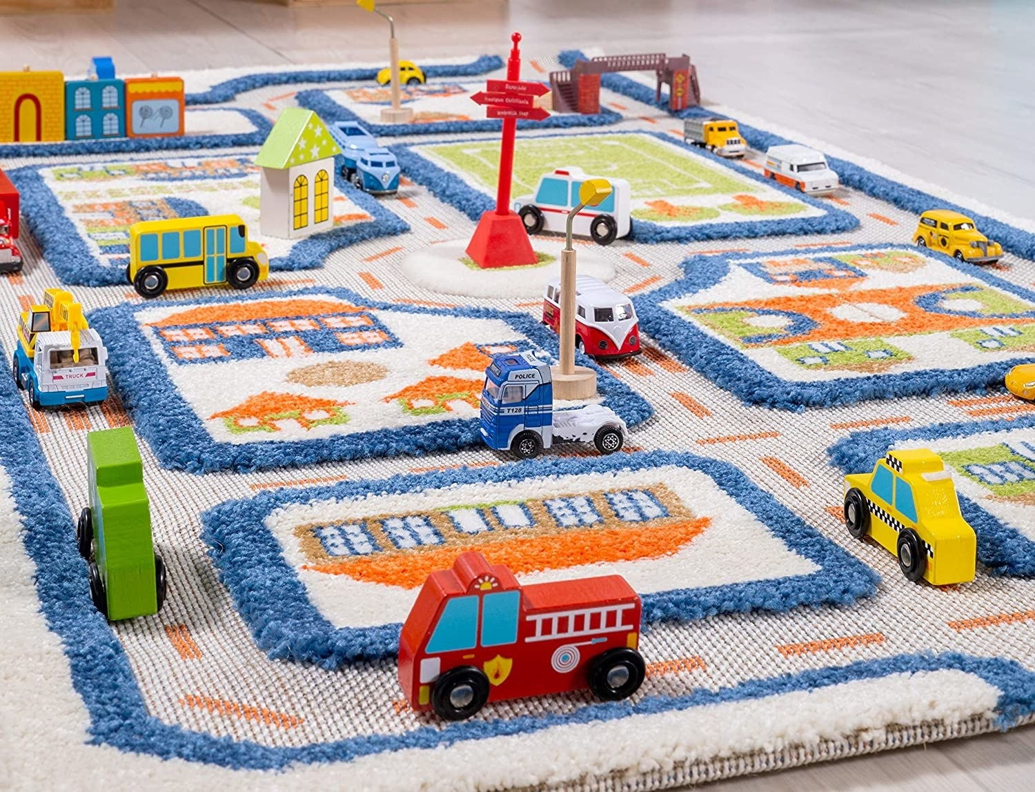 Colorful carpet that looks like a town with toy cars on streets