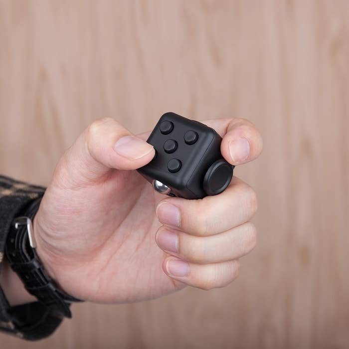A person with the fidget cube in their hand.