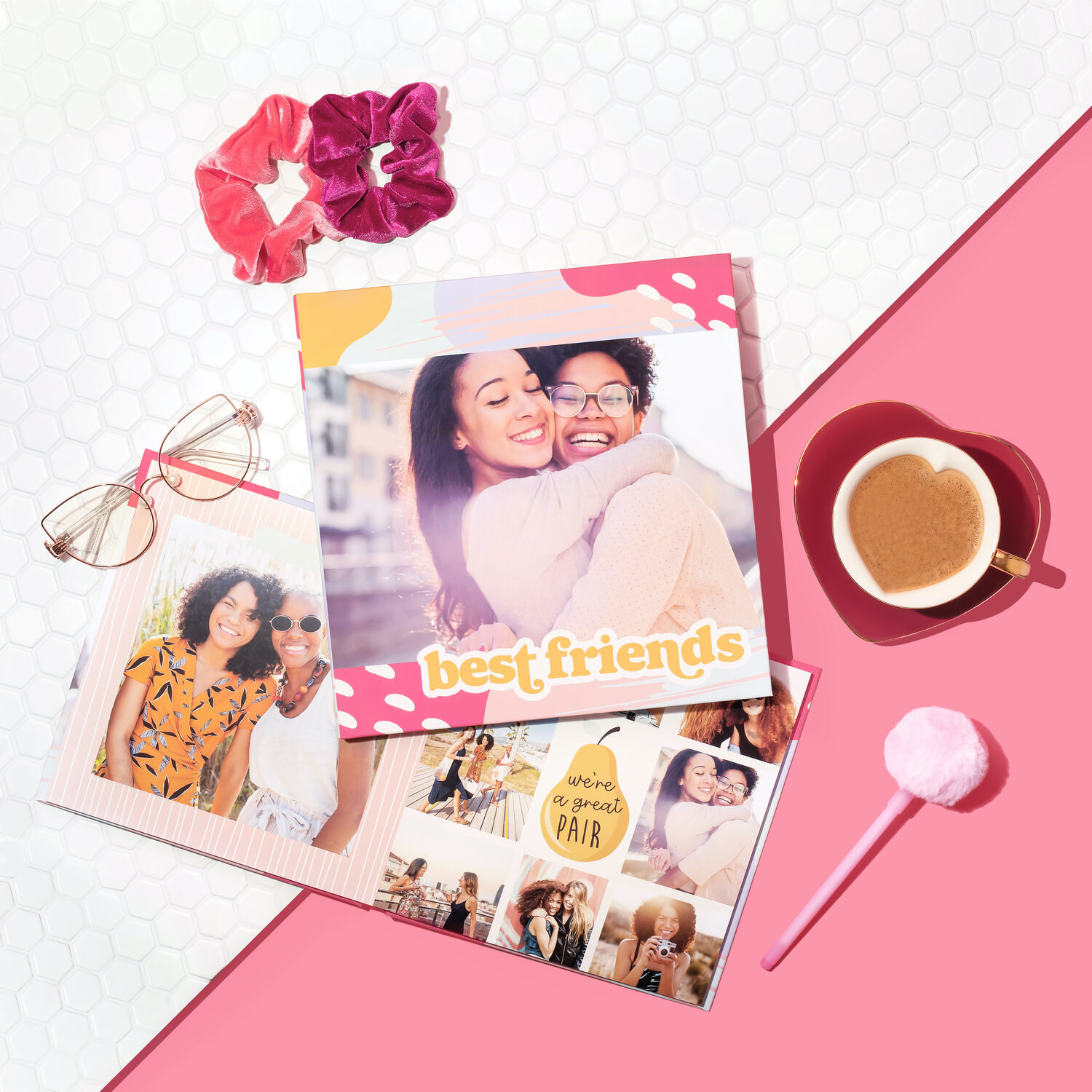 Photo book samples on pink background with various accessories