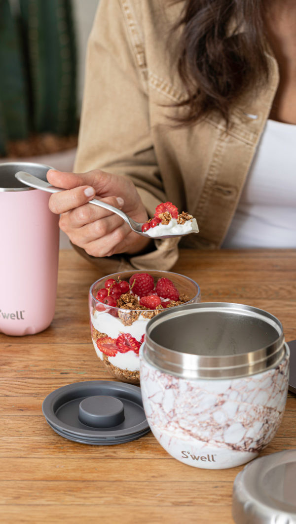 A model eats parfait out of the inner prep bowl while the exterior stainless steel bowl sits nearby