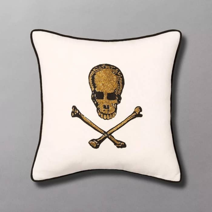 The skull and bones throw pillow in white with gold embroidery