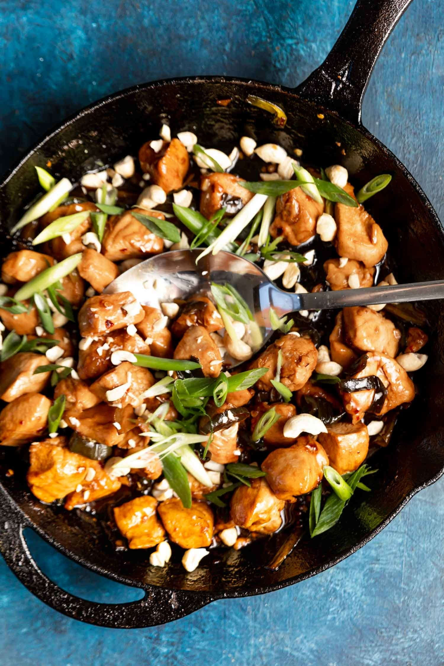 A skillet of Kung Pao chicken with cashew nuts and scallions.