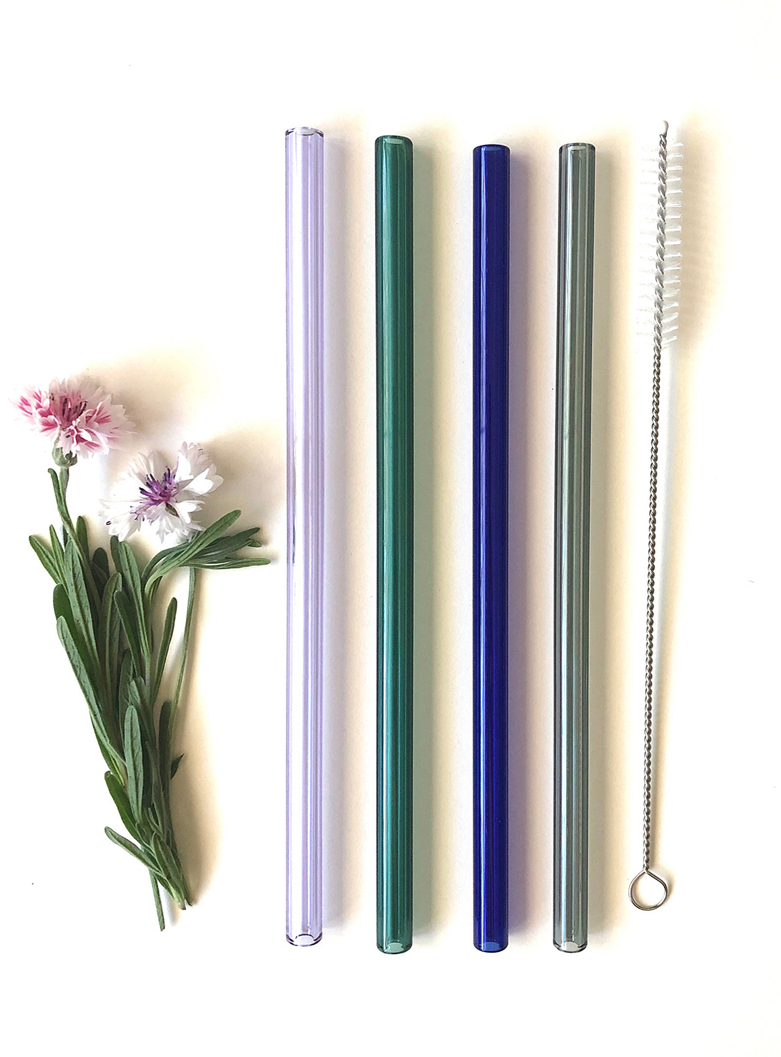 A set of four glass straws and a small cleaning brush on a plain background