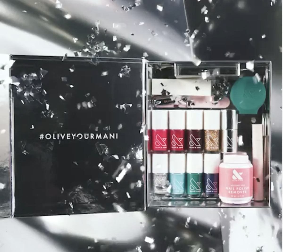 The silver box filled with nine nail polish bottles in different colors and all the assorted tools that are included in the box