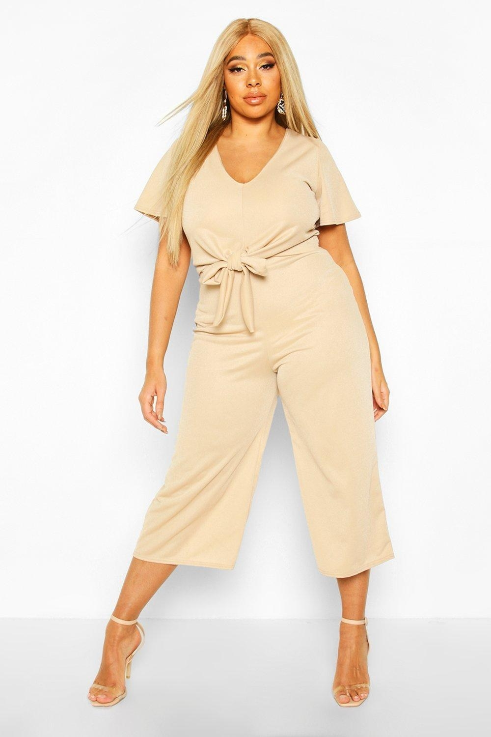 a model in a tan colored jump suit with angel sleeves and a tied bow in the front