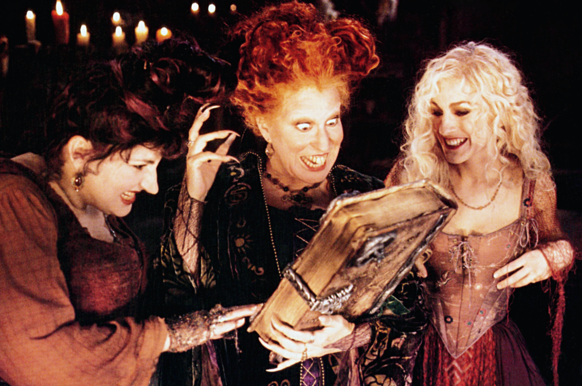 "Bette Midler as Winifred ""Winnie"" Sanderson, Sarah Jessica Parker as Sarah Sanderson, and Kathy Najimy as Mary Sanderson in the movie ""Hocus Pocus."""