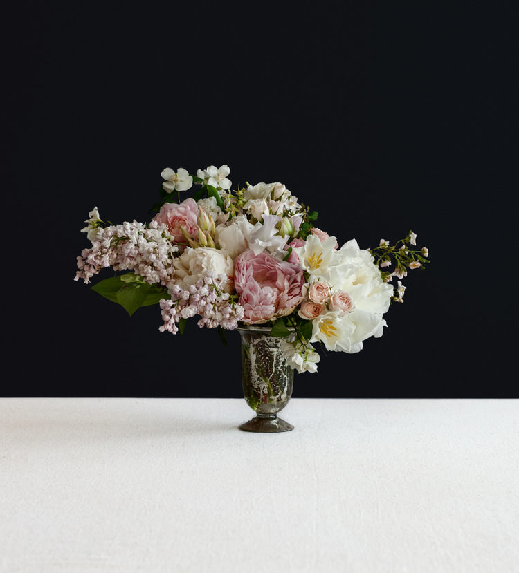 A bouquet of fresh flowers in white and pink in a black vase