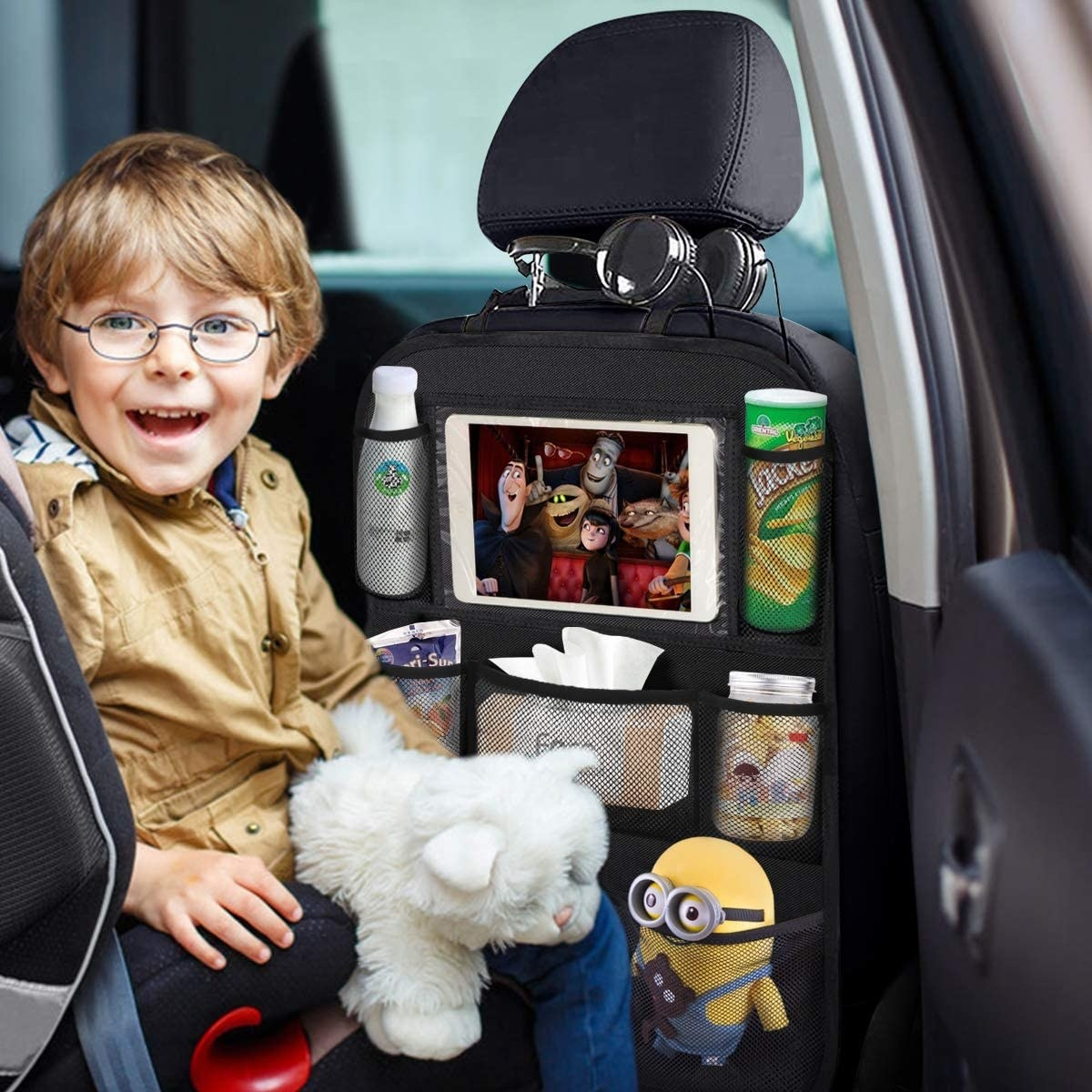 kid in backseat of car with a bunch of stuff available in the backseat organizer