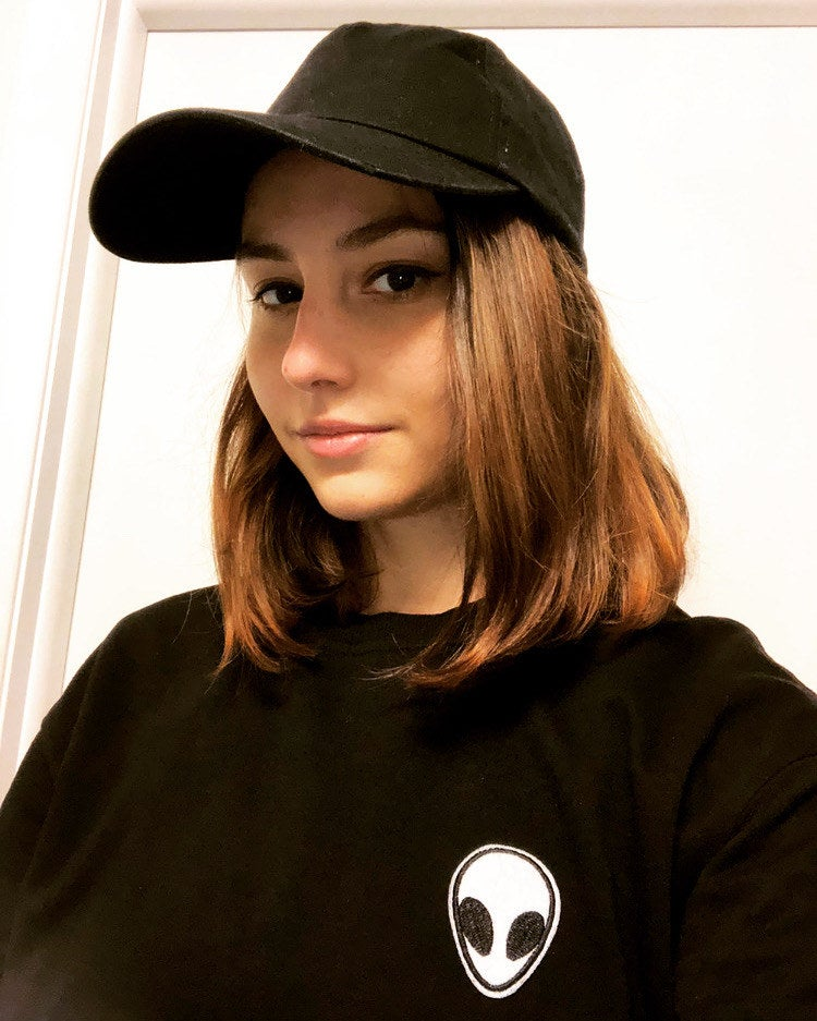 buzzfeed writer wearing a black baseball cap and black sweatshirt with an alien patch on the front