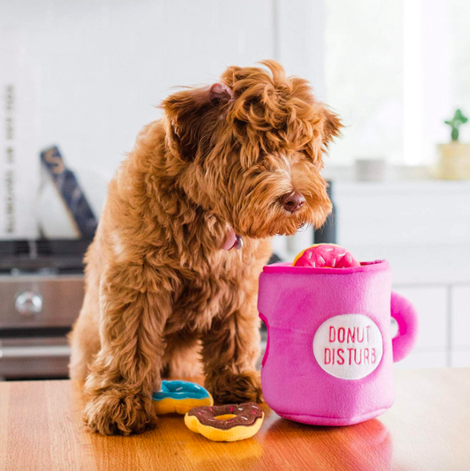 """Fluffy brown dog hovers over pink mug-shaped squeak toy that says """"Donut Disturb"""" and plush brown, pink, and blue sprinkle donuts"""