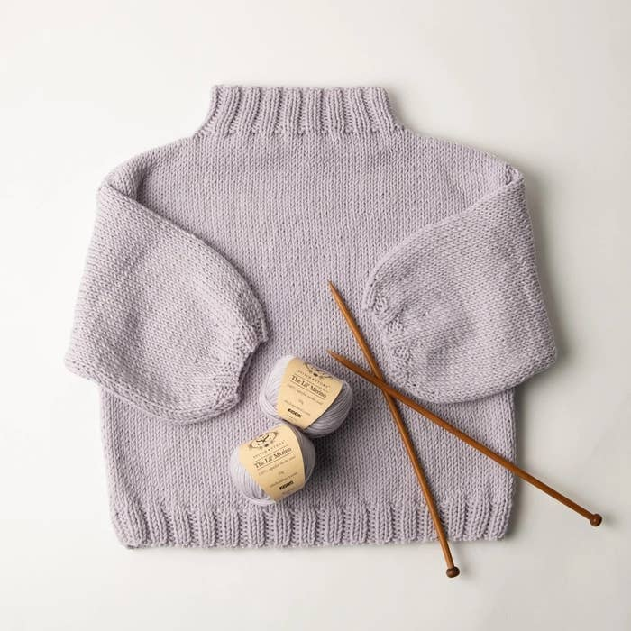 Yarn and knitting needles laid on top of a gray sweater