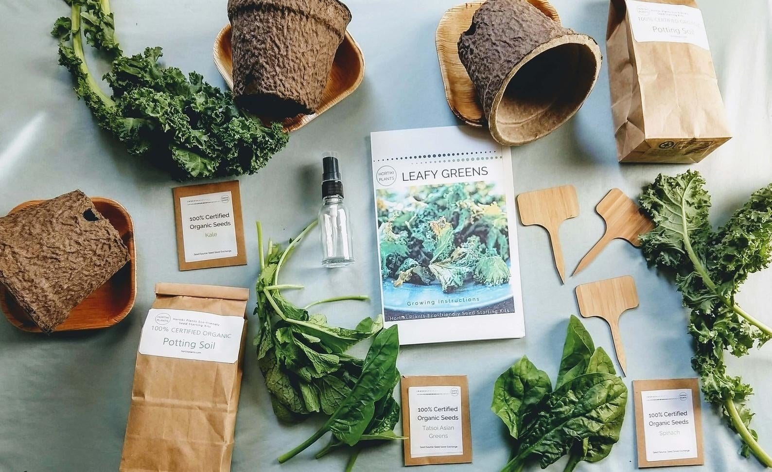 """An instruction packet that reads """"Leafy Greens"""" surrounded by a collection of pots, trays, soil, and seed packets"""