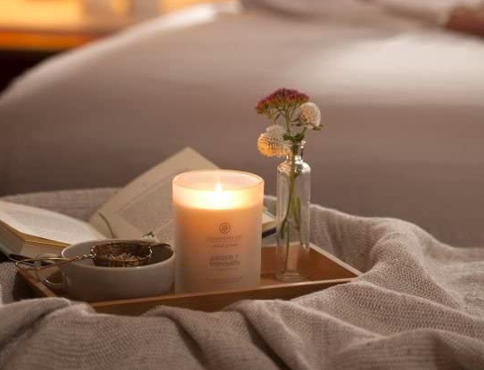 Chesapeake Bay Peace + Tranquility candle lit on a bedside tray with a vase and gray bowl