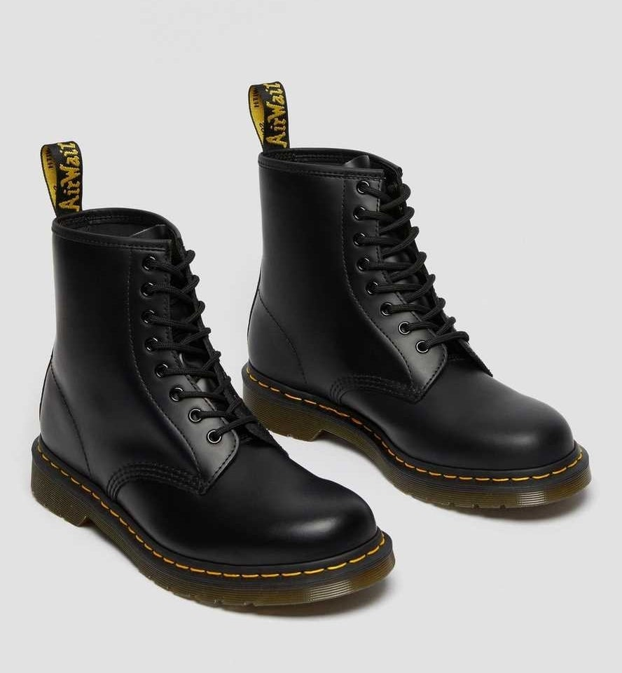 black lace up combat boots with thick soles and yellow stitching
