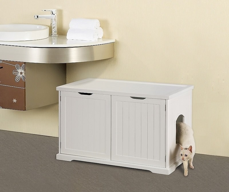 A short white cabinet with two doors that fits under a sink; a cat is coming out of a doorway on the side