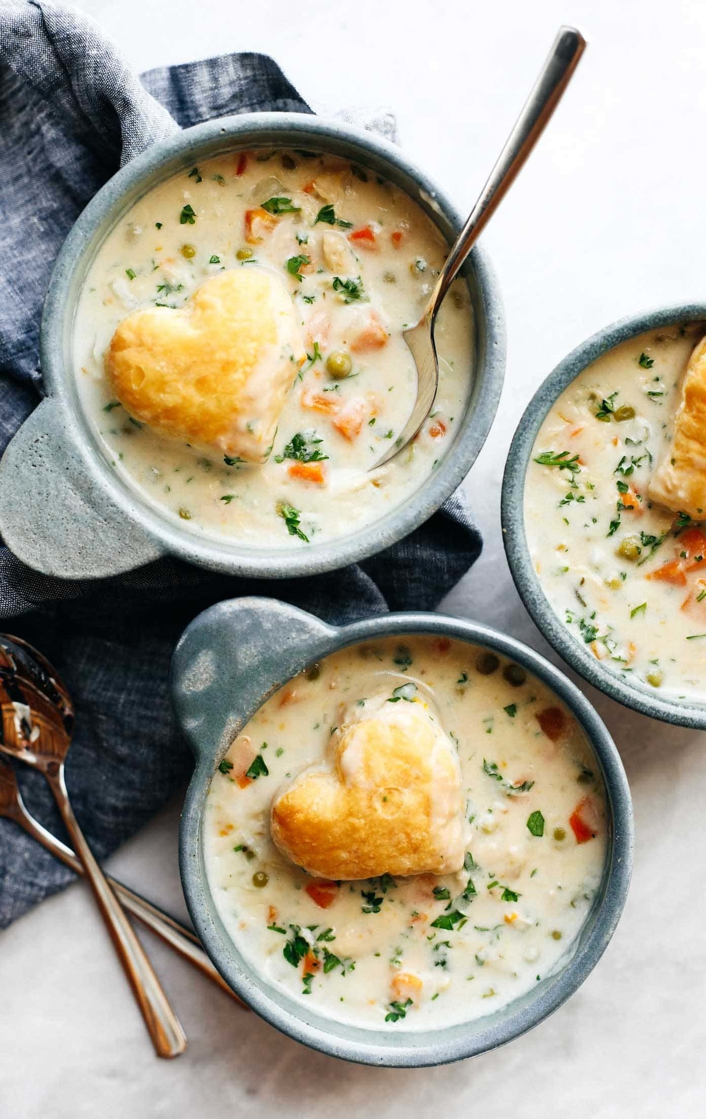 A bowl of chicken pot pie soup with a heart-shaped biscuit on top