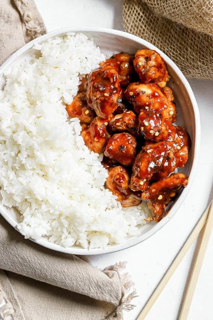 A bowl of white rice with crispy General Tso's chicken.