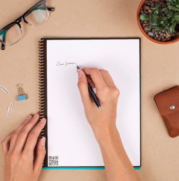 Hands sketch letter on smart reusable notepad