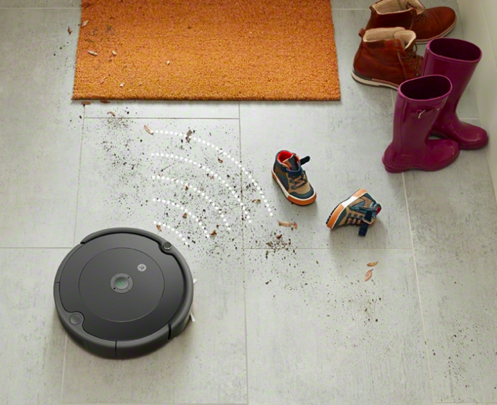 Black robot vacuum moves toward leaf and debris on a gray floor next to boots