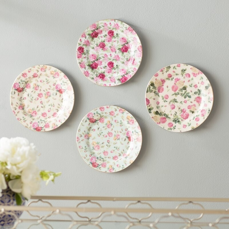 A set of four ivory and pale green plates with vintage pink rose painted patterns