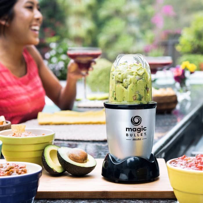 magic bullet mini blender with guacamole in it with a person drinking a cocktail in the background