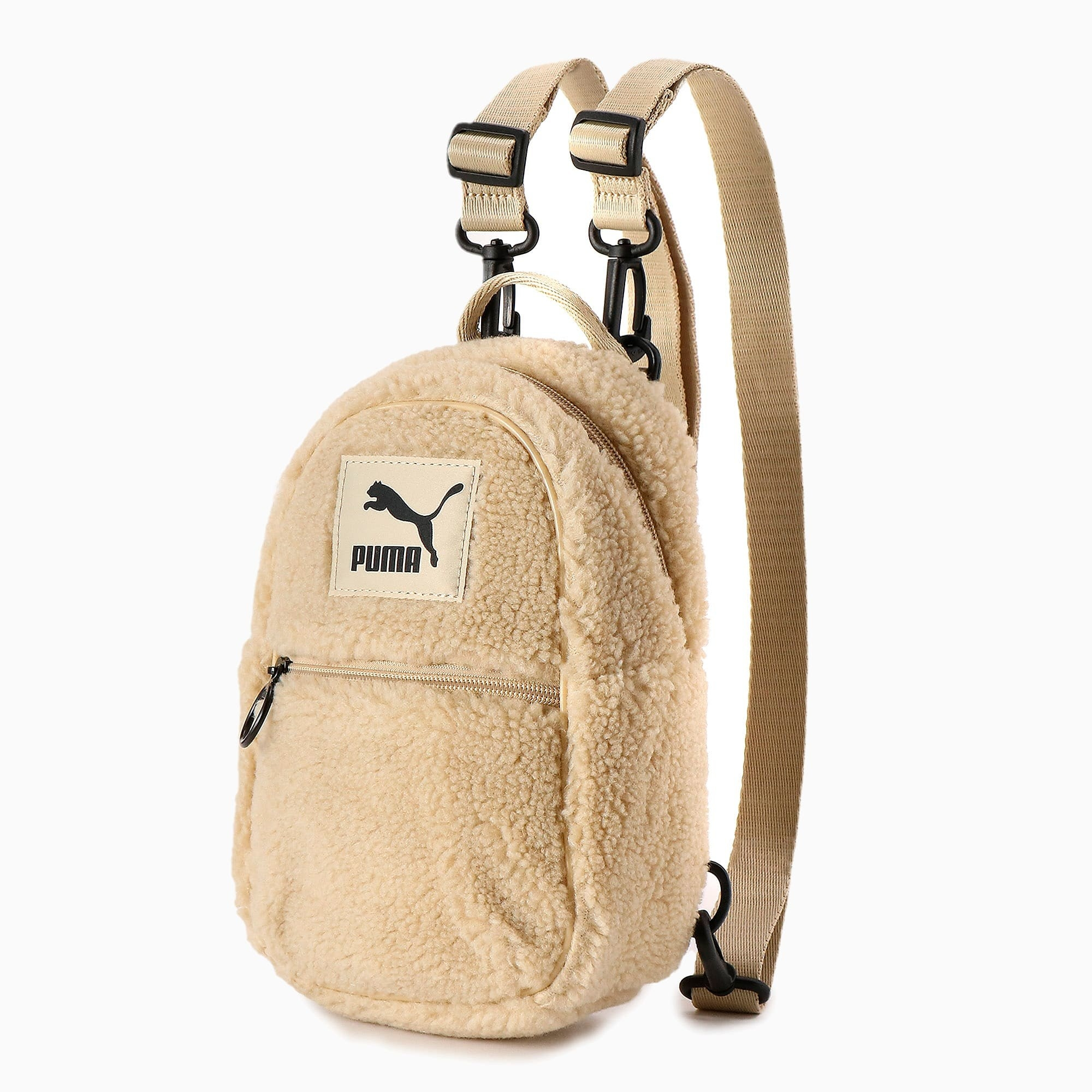 The small beige oval-shaped backpack with a front zippered pocket, top handle, and two straps with clips on them
