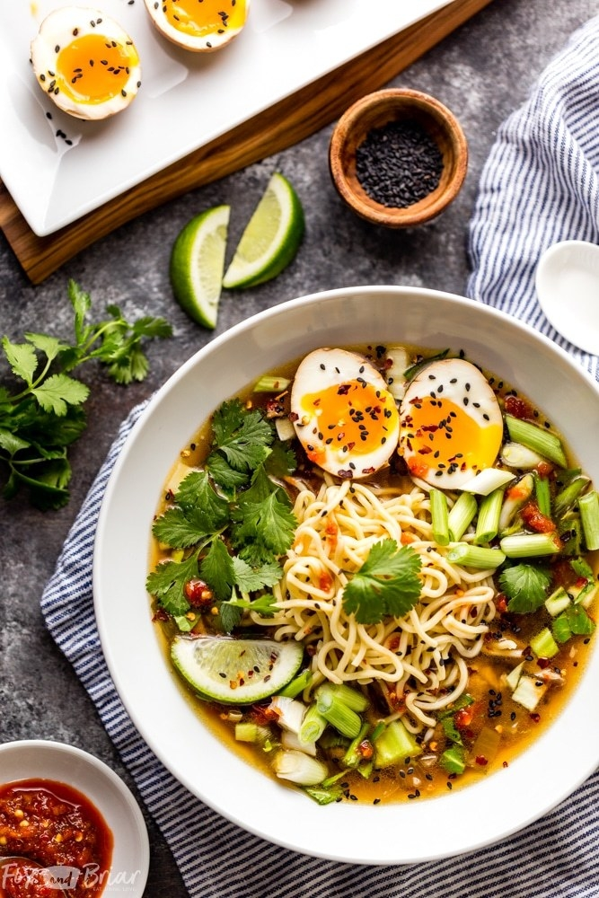 A bowl of ramen with scallions, sesame seeds, cilantro, and soft boiled egg.